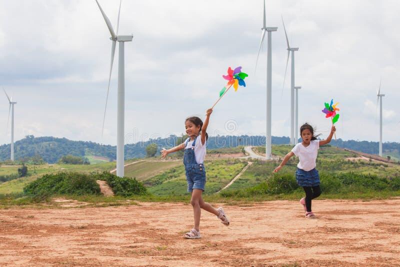 两个亚裔儿童女孩是一起跑和使用与风轮机玩具在风轮机领域 免版税库存图片