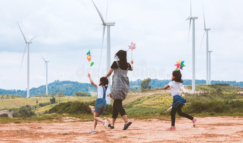 两个亚裔女孩和他们的母亲是跑和使用与风轮机玩具与在风轮机领域的乐趣一起 库存照片