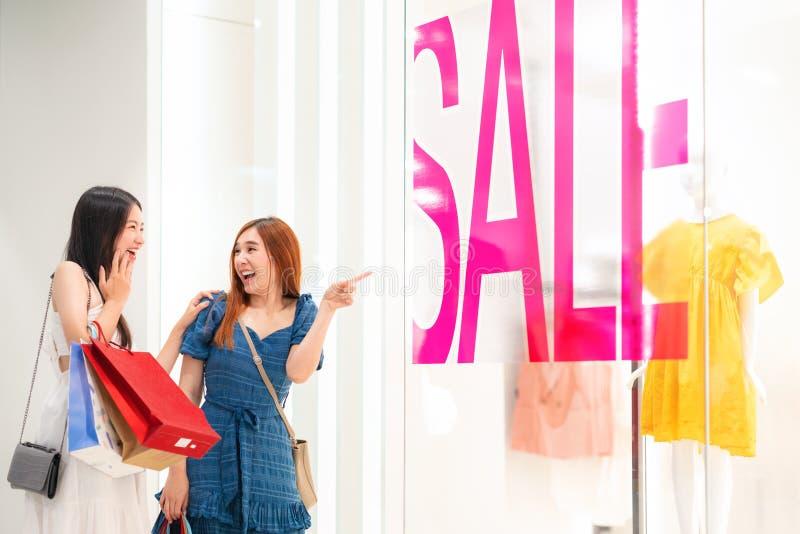 两个亚裔朋友去的旅行和购物在折扣百货店 库存照片