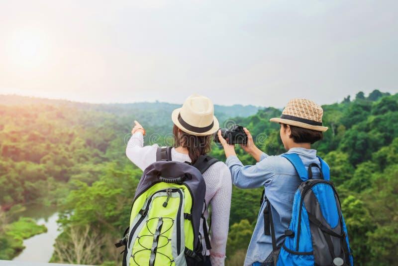两个亚裔游人为山的森林照相 在假日概念的旅行 免版税库存图片