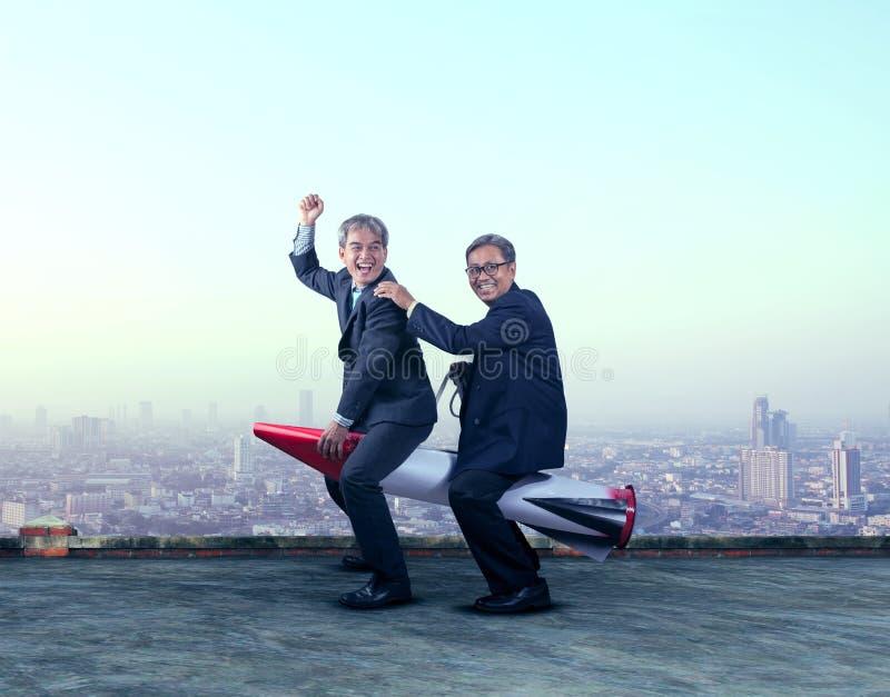 两个亚洲人商人滑稽使用与在buil的火箭导弹 免版税库存图片