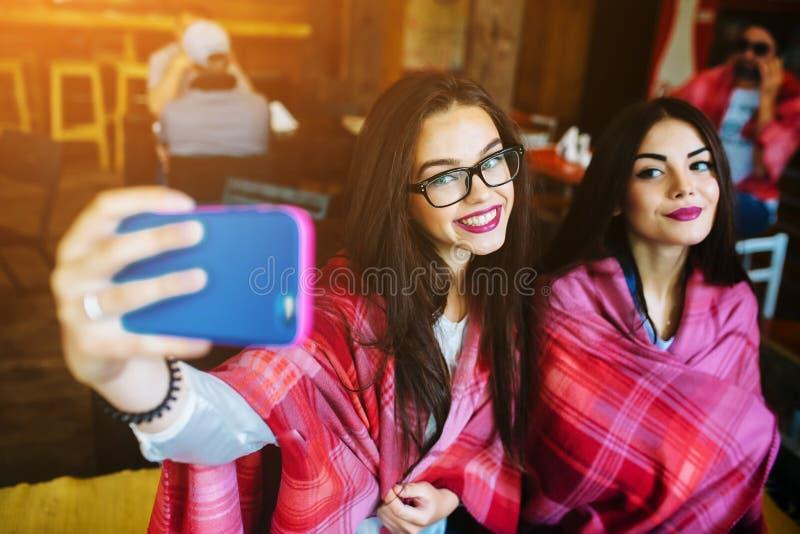 两个亲密的朋友做在咖啡馆的selfie 免版税图库摄影