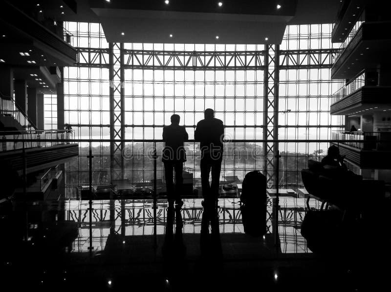 两个人剪影在一个巨大的窗口里 库存照片