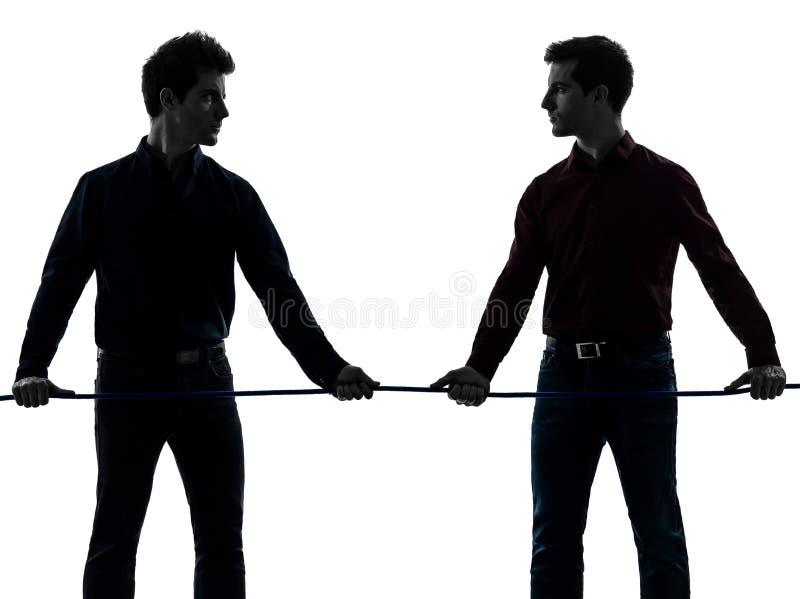 两个人双胞胎朋友拔河剪影 免版税图库摄影