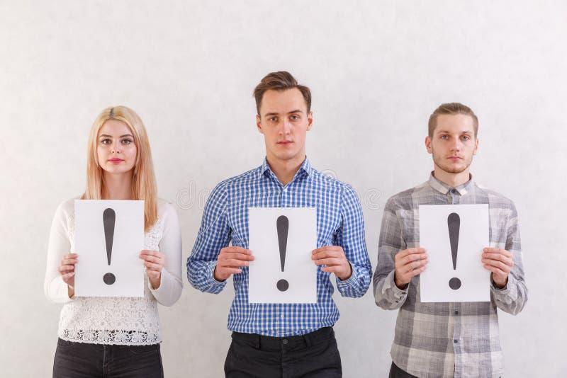 两个人和女孩站立在旁边保留与惊叹号的板料在灰色背景 免版税图库摄影