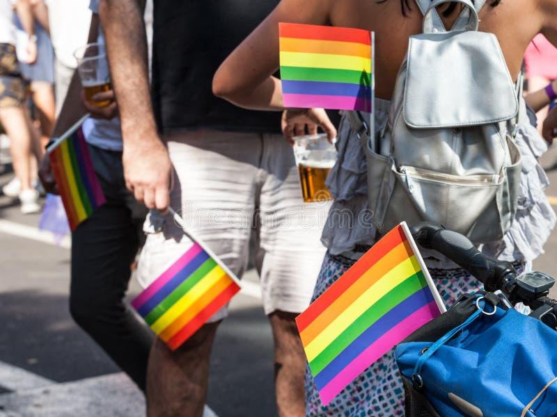 两个人和妇女藏品彩虹快乐旗子在他们的口袋在同性恋自豪日期间 免版税库存照片