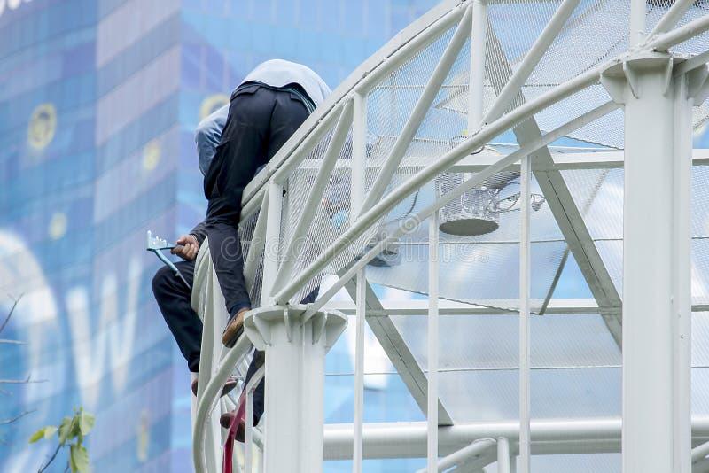 两个人在一个高屋顶工作 免版税库存照片