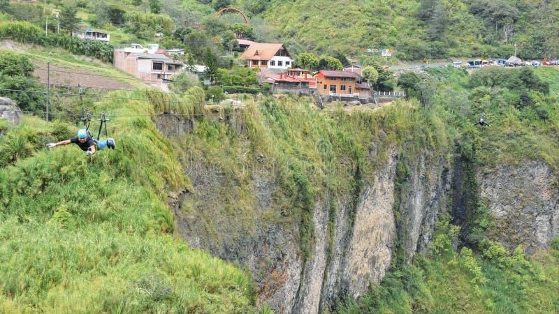 两个人在通古拉瓦火山,厄瓜多尔,南美横渡在一zipline的小瀑布 库存图片
