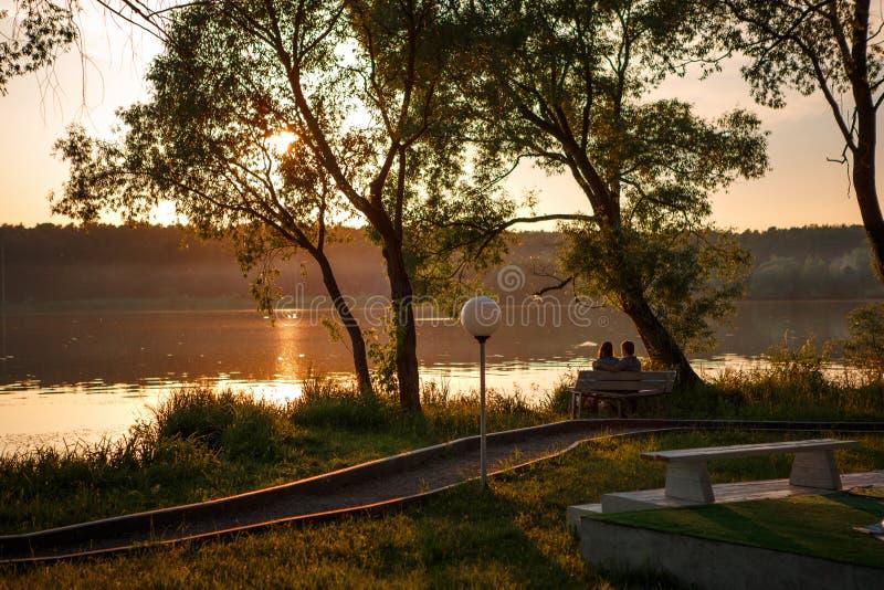 两个人坐一条长凳在江边的公园在日落 免版税库存照片
