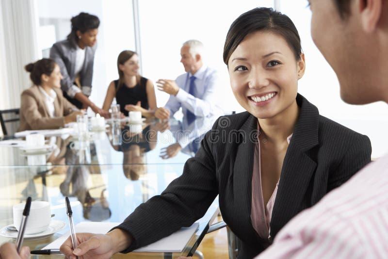 两个人开会议在玻璃表附近在有同事的会议室在背景 免版税库存图片