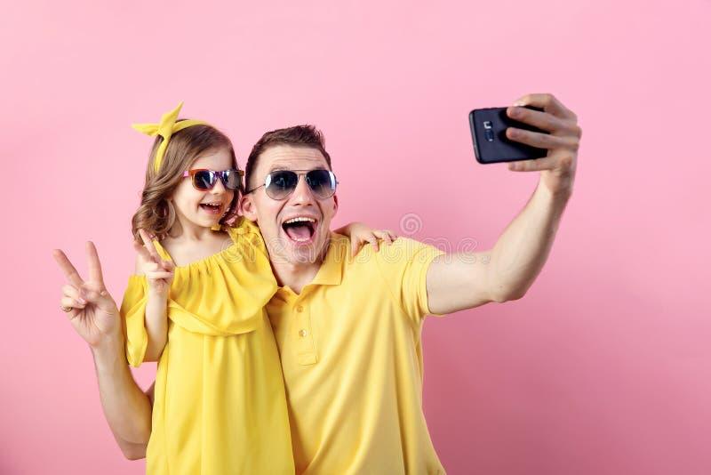 两个人愉快的家庭画象  做与智能手机的爸爸和小女儿selfie 水平的颜色 库存照片