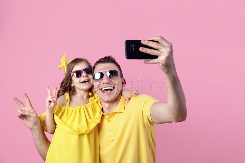 两个人愉快的家庭画象  做与智能手机的爸爸和小女儿selfie 水平的颜色 库存图片