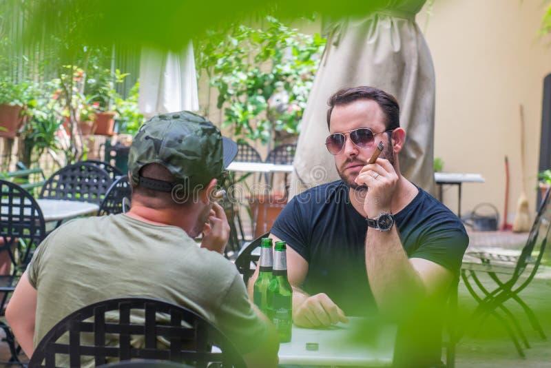 两个人抽雪茄和饮用的啤酒-无固定职业的摄影师射击 免版税库存照片