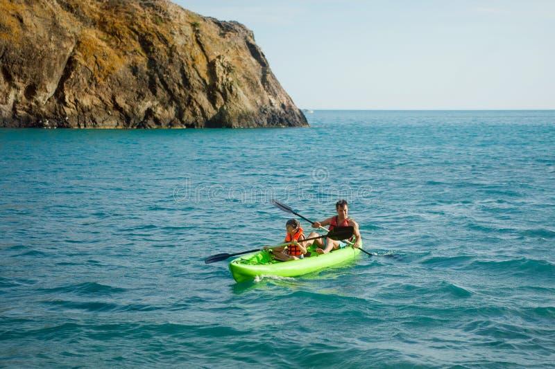 两个人用浆划在海的一艘皮船 划皮船在海岛上 免版税库存照片
