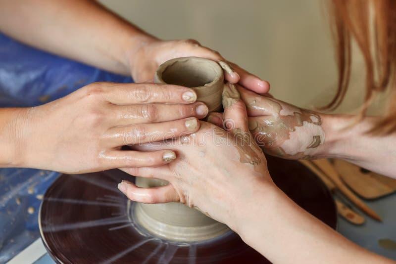 两个人的手创造罐,陶瓷工` s轮子 教的瓦器 库存照片