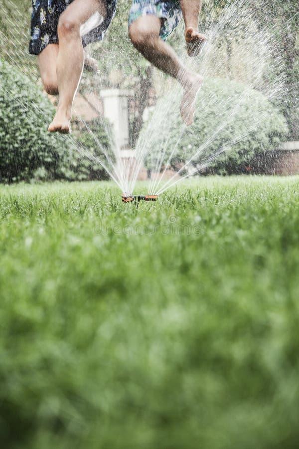 两个人跳跃通过喷水隆头的,空中,表面平实射击 库存图片