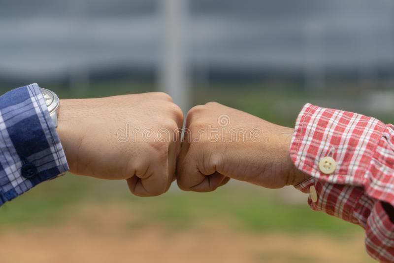 两个人采取了拳头爆沸,年轻人的手显示力量 免版税库存图片