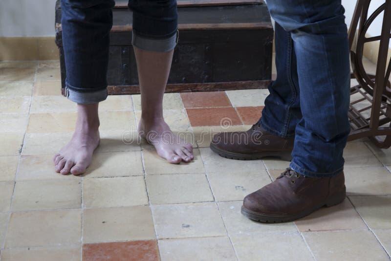 两个人,他们中的一个赤足和棕色起动的另一个人的脚的细节 免版税库存图片