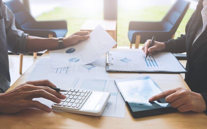 两个企业同事谈论关于股票市场数据研究在现代办公室 免版税图库摄影
