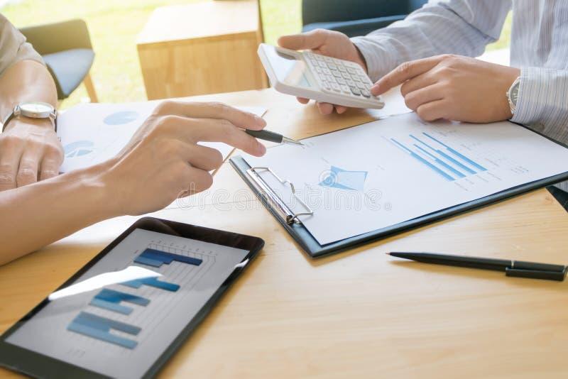 两个企业同事谈论关于股票市场数据研究在现代办公室 免版税库存图片