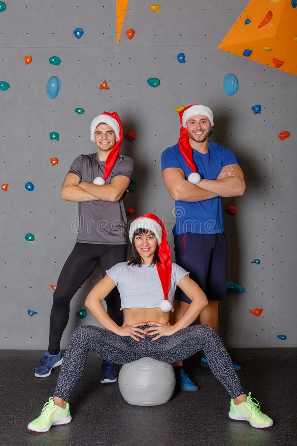两个体育人和红色圣诞老人帽子的微笑和摆在对墙壁的一个女孩上升的 免版税库存图片