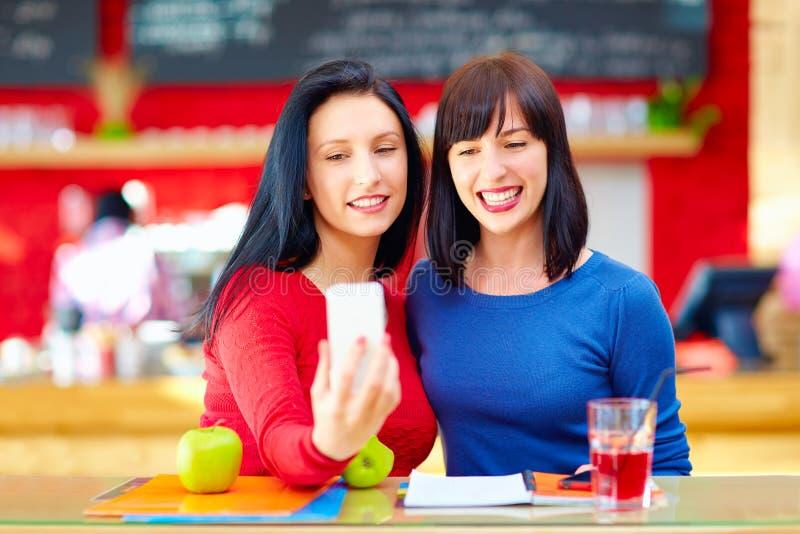 两个俏丽的女孩,采取在巧妙的电话的朋友selfie,当坐在咖啡馆时 免版税库存图片