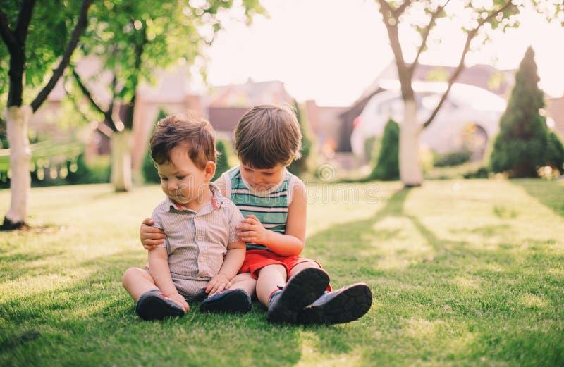 两个兄弟一起坐草 免版税库存图片