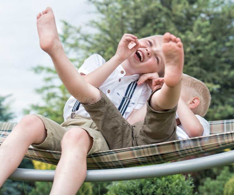 两个兄弟休息并且获得乐趣 孩子在吊床乘坐 ï ¿ ¼ 免版税库存照片