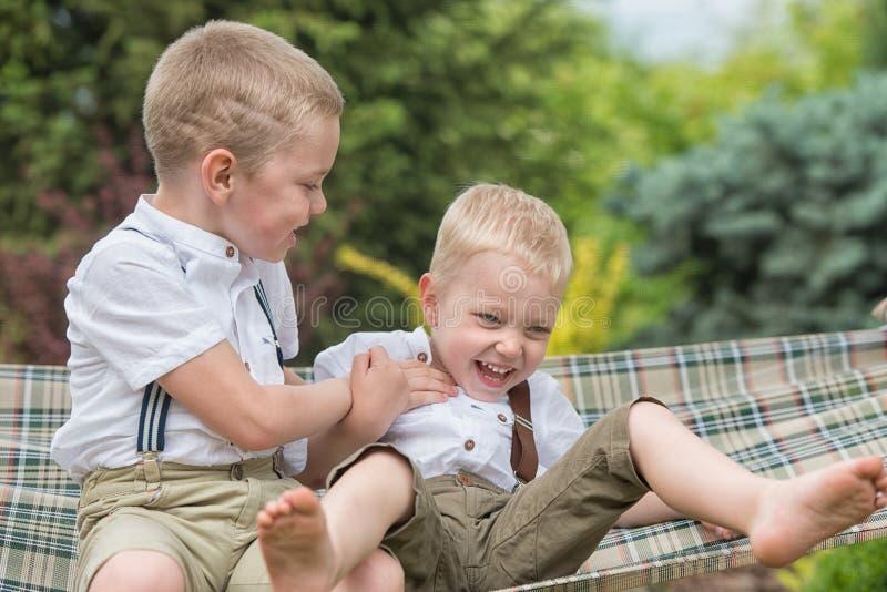 两个兄弟休息并且获得乐趣 孩子在吊床乘坐 库存照片