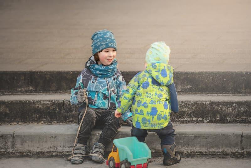 两个兄弟使用与玩具汽车在台阶,暗淡 库存图片