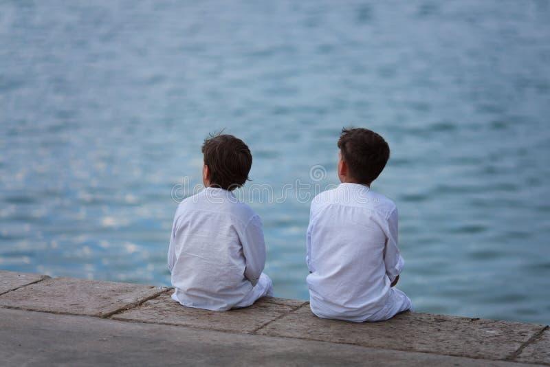 两个兄弟坐海滩并且看海 库存照片