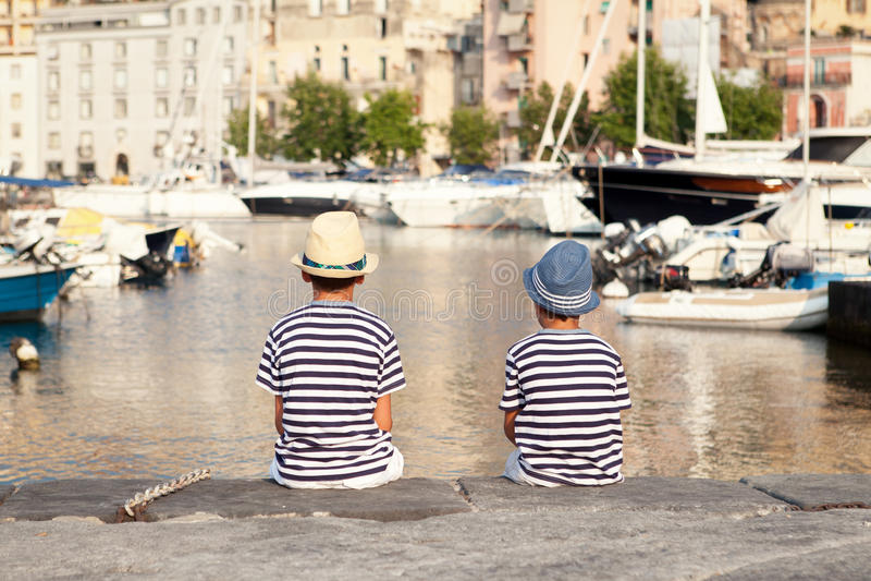 两个兄弟拥抱并且看船,海上的游艇 库存图片
