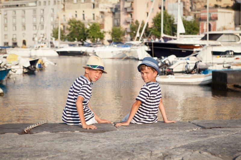 两个兄弟拥抱并且看船,海上的游艇 免版税库存图片
