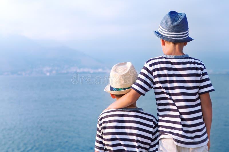 两个兄弟拥抱并且看船,海上的游艇 图库摄影