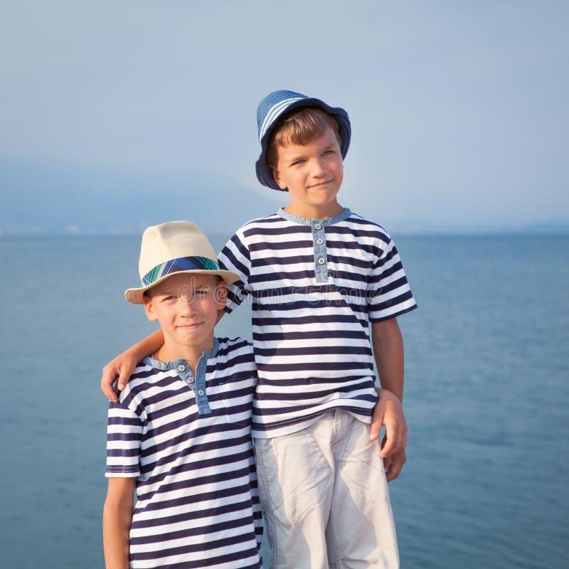 两个兄弟拥抱并且看船,海上的游艇 免版税库存照片