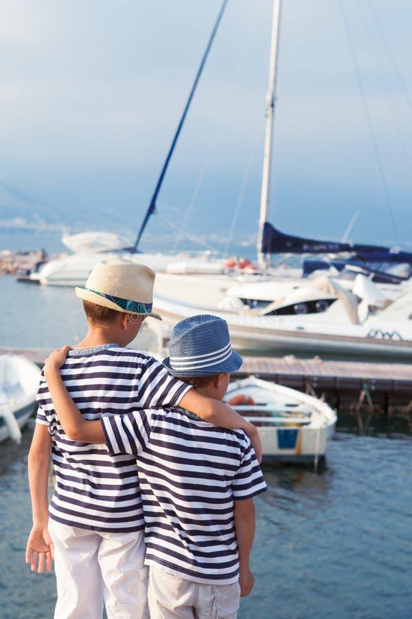 两个兄弟拥抱并且看船,海上的游艇 库存照片