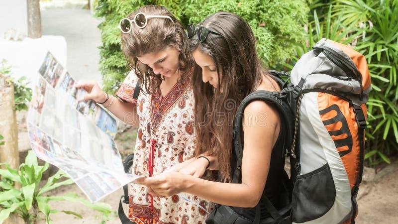 两个冒险旅客妇女背包徒步旅行者看旅游地图 免版税库存照片