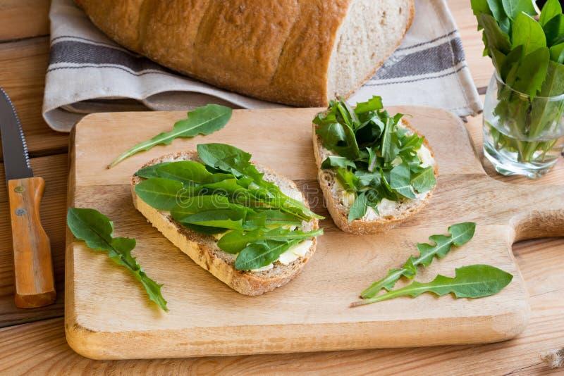两个切片与黄油和蒲公英叶子的酸面团 图库摄影