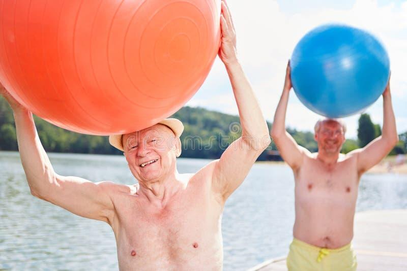 两个前辈做着与健身房球的体操 免版税图库摄影