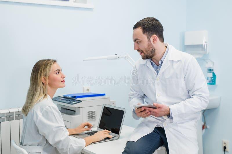 两个医生同事在工作地点坐并且为他们的工作使用现代技术,在白色外套,被聚焦 库存图片