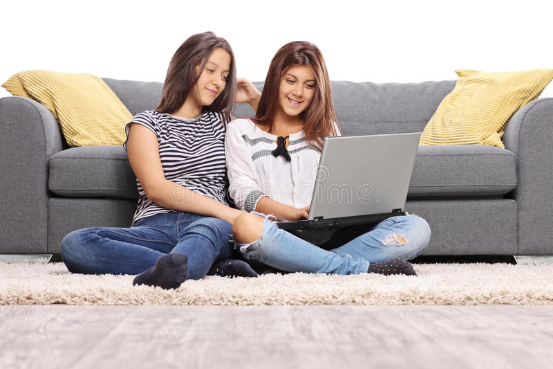 两个十几岁的女孩坐地板 免版税图库摄影