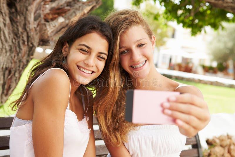 两个十几岁的女孩坐采取Selfie的长凳在公园 图库摄影