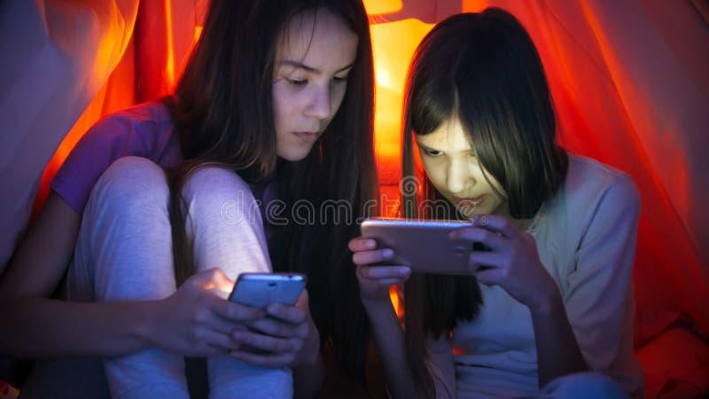 两个十几岁的女孩画象有巧妙的电话的在毯子下在晚上 图库摄影