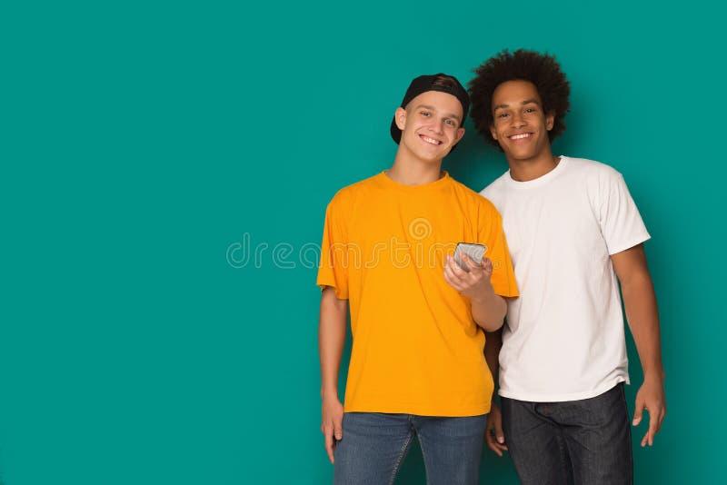 两个十几岁的男孩演播室画象使用smatphone的 免版税库存照片