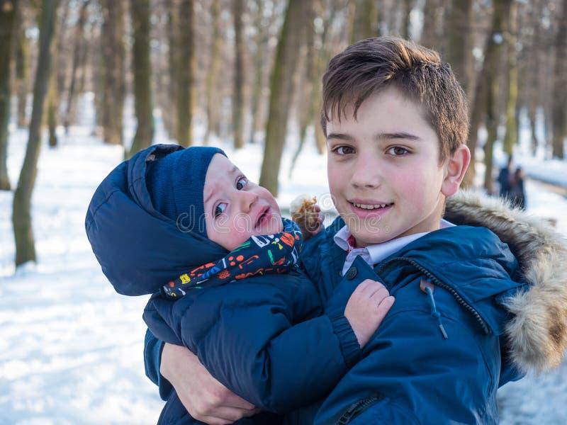两个可爱的兄弟在冬天公园 免版税库存照片