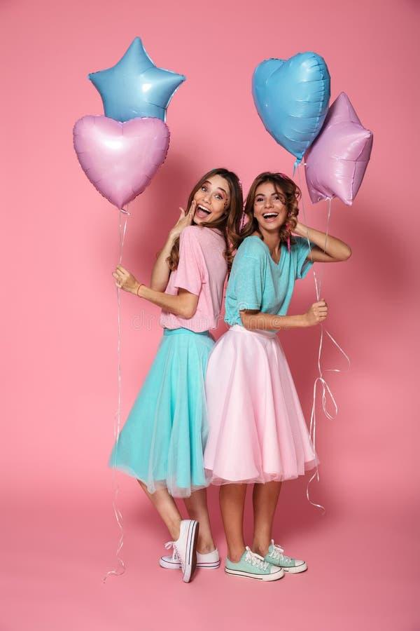 两个可爱的女孩在明亮的五颜六色的衣裳穿戴了 免版税图库摄影