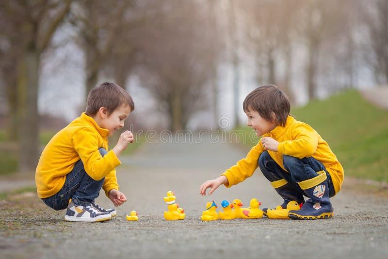 两个可爱的孩子,男孩兄弟,使用在有橡胶的公园 免版税库存图片