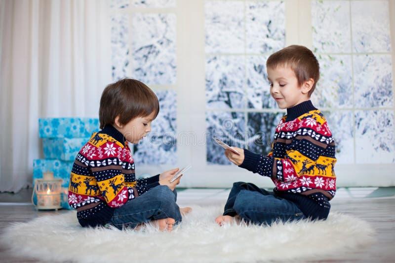 两个可爱的孩子,男孩兄弟,纸牌在家, wint 免版税库存图片
