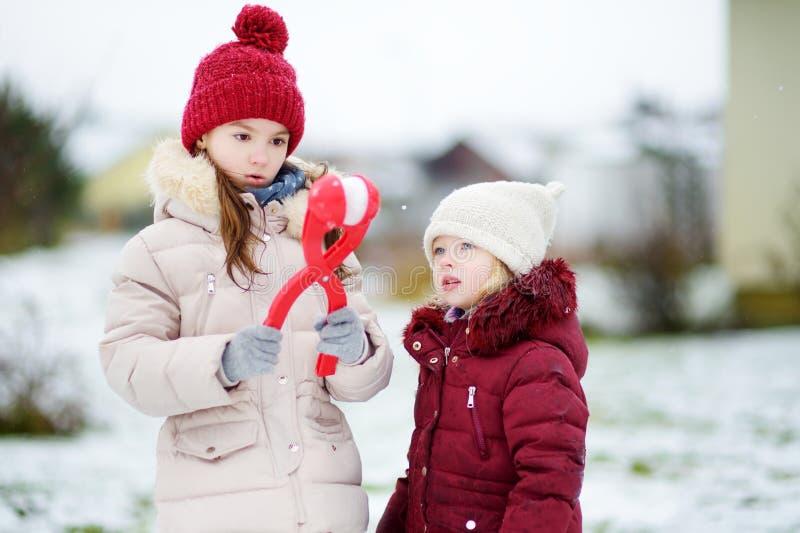 两个可爱的小女孩获得与雪球制造商的乐趣在美丽的冬天公园 使用在雪的美丽的姐妹 免版税库存照片