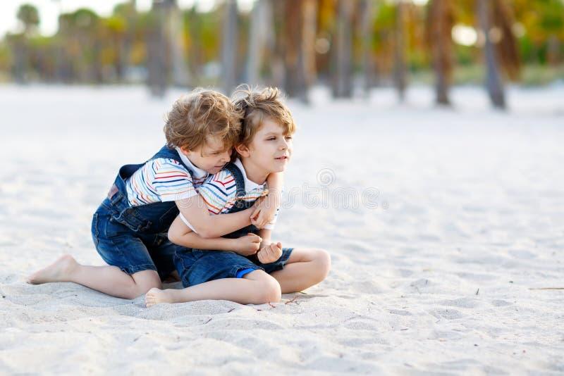 两个可爱的弟弟坐在热带海滩的沙子,愉快的最好的朋友,哄骗使用的男孩,友谊概念 库存照片